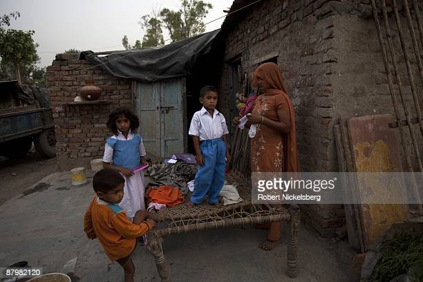 Children get ready for school in a slum area near a newly dug roadway April 21 2009 where agricultural areas members of twelve families have been...