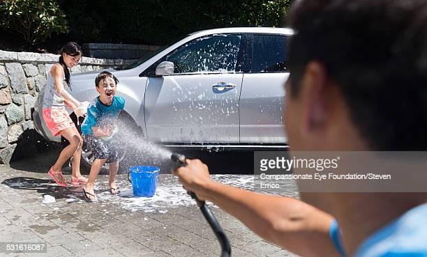 children getting sprayed washing car - courtyard - fotografias e filmes do acervo