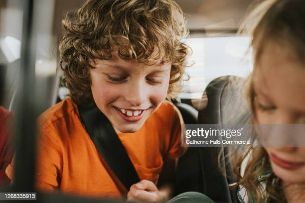 children giggling in the back seat of a car - car stock pictures, royalty-free photos & images