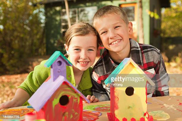 Children, Girl and Boy Painting Playful Wooden Birdhouse Craft Project