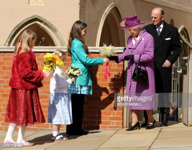 Children give flowers to Britain's Queen Elizabeth II as she leaves with Prince Philip, the Duke of Edinburgh an Easter Sunday church service in...