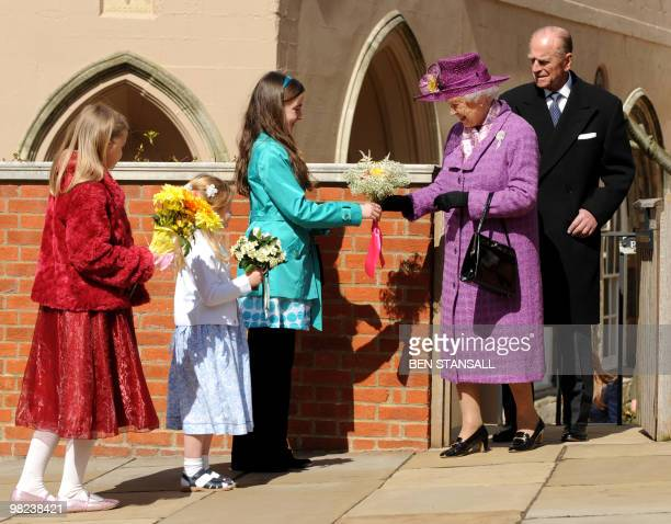 Children give flowers to Britain's Queen Elizabeth II as she leaves with Prince Philip the Duke of Edinburgh an Easter Sunday church service in...