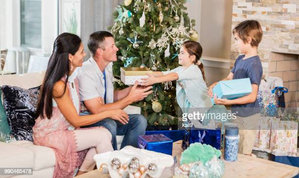 children giving christmas presents to parents - florida christmas stock pictures, royalty-free photos & images