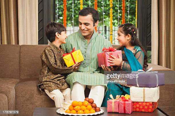 children giving gifts to their father on diwali - diwali sweets stock photos and pictures