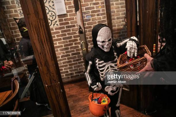 """Children go trick-or-treat at a restaurant on Halloween, October 31, 2019 in New York City. Halloween, which is named from """"All Hallows' Eve"""", falls..."""