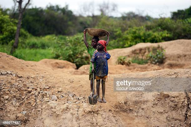 Children gold miners wait on May 5 2014 before coming down into a traditional mine in the village of Gam where gold mining is the main business...