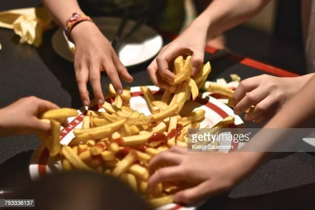 children grabbing french fries - batata frita lanche - fotografias e filmes do acervo