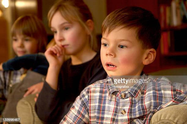 children group watching tv, focus at the boy in front