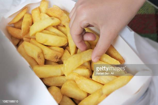 children hands picking french fries - rafael ben ari stock pictures, royalty-free photos & images