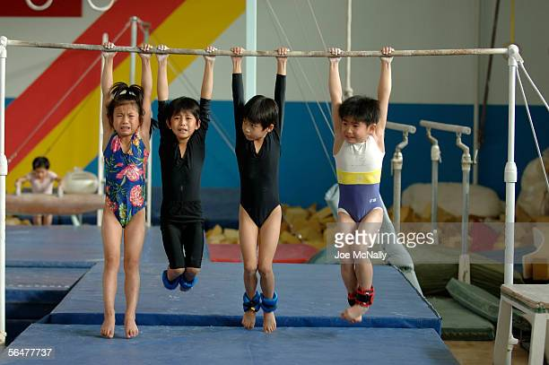 Children hang from a bar during training September 23, 2005 in Beijing, China. Established in 1958, Shi Chahai has built a world class reputation for...