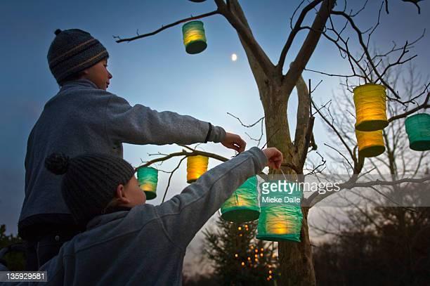 children hanging paper lanterns in a tree