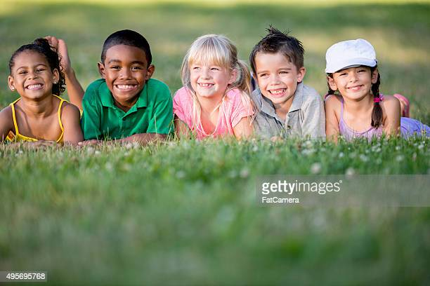 Children Happily Sitting on a Grassy Hill
