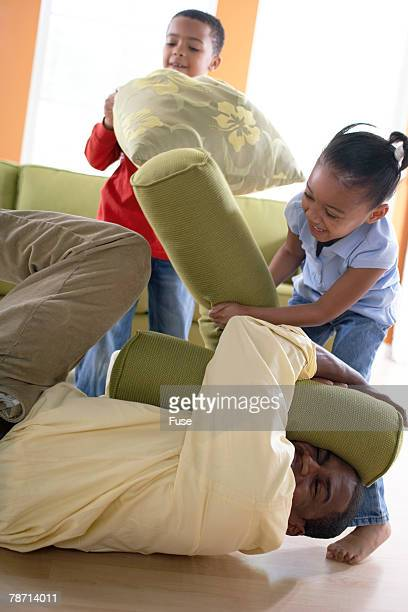 Children Having a Pillow Fight with Their Father