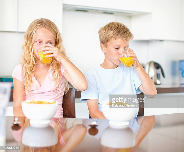 Children having breakfast of cereal and juice