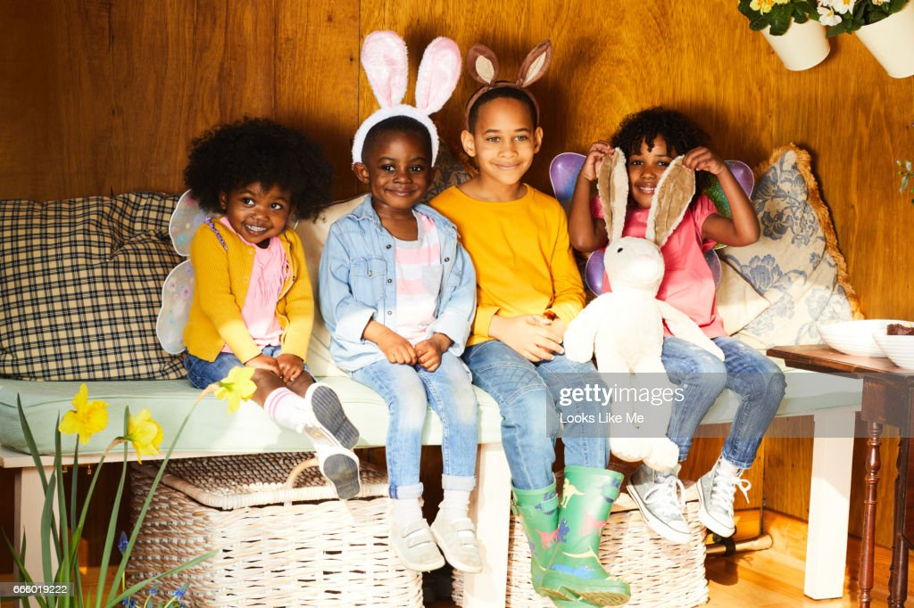 Children having Easter fun with bunny ears in the summer house in the garden.