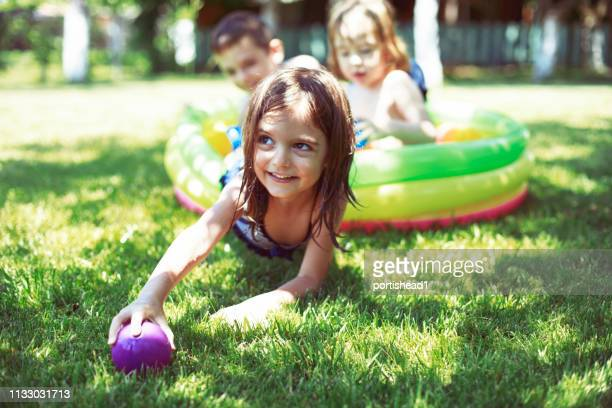 children having fun in inflatable swimming pool - kids pool games stock pictures, royalty-free photos & images