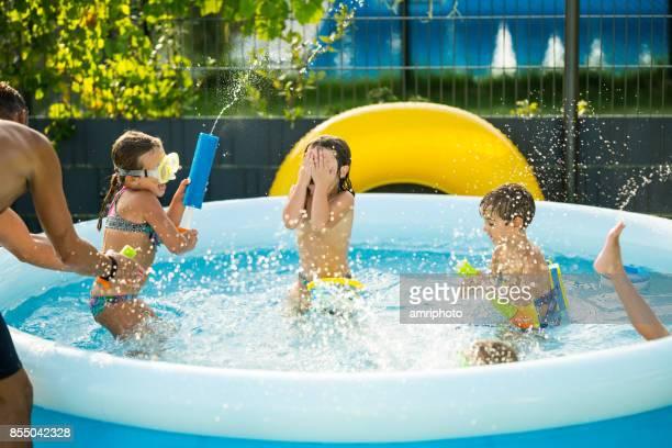 children having fun in pool at home in garden
