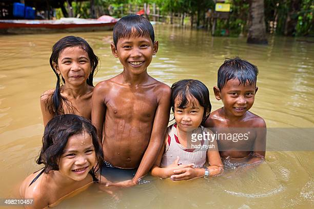 Children having fun in the water during flood, Cambodia