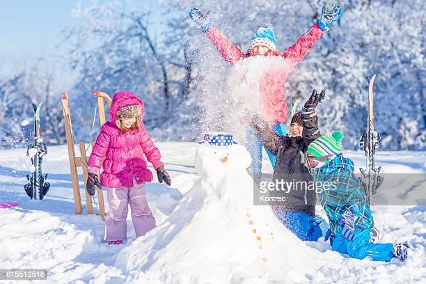 les enfants s'amuser en hiver - bonhomme de neige photos et images de collection