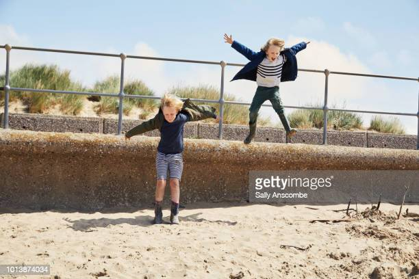 Children having fun jumping from a wall onto the beach
