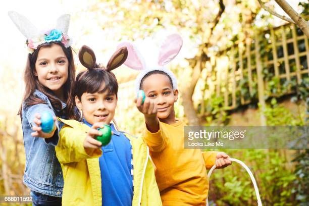 children having fun on an easter egg hunt. - chasse aux oeufs de paques photos et images de collection