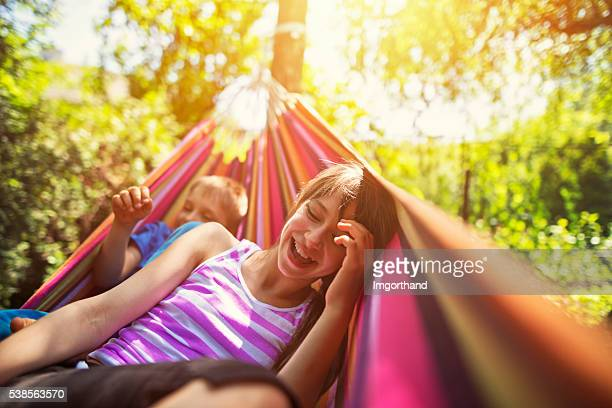 Children having fun on hammock on summer day