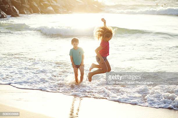 children having fun on the beach - rabbit beach stock photos and pictures