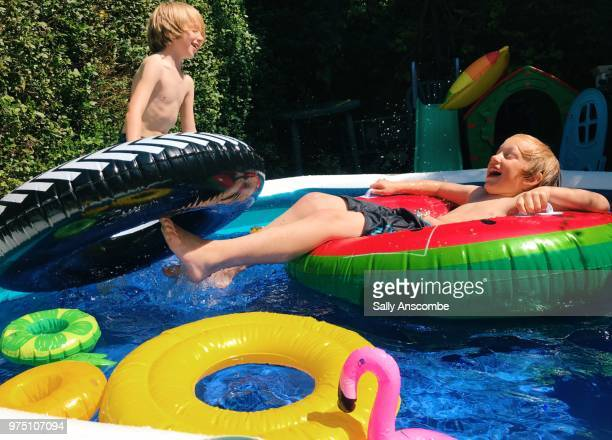 children having fun playing in a paddling pool - kids pool games stock pictures, royalty-free photos & images