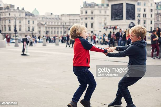 children having fun playing in trafalgar square - courtyard stock photos and pictures