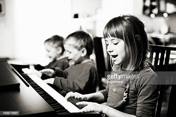 Children having fun playing the piano and singing