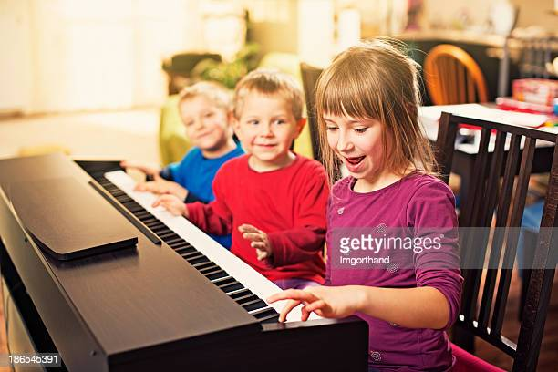 children having fun playing the piano - keyboard player stock photos and pictures