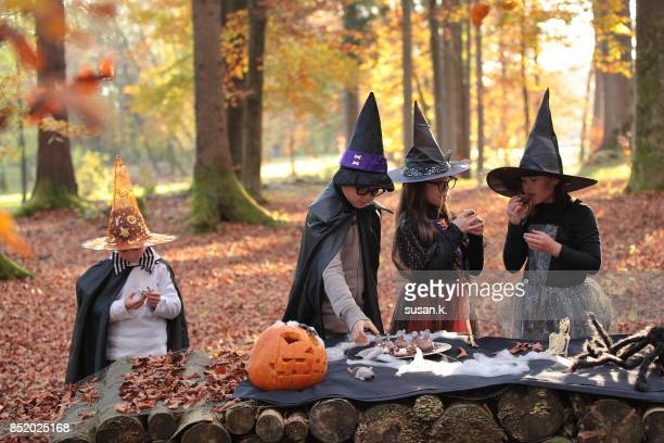 children having halloween party in the woods. - halloween party stock photos and pictures