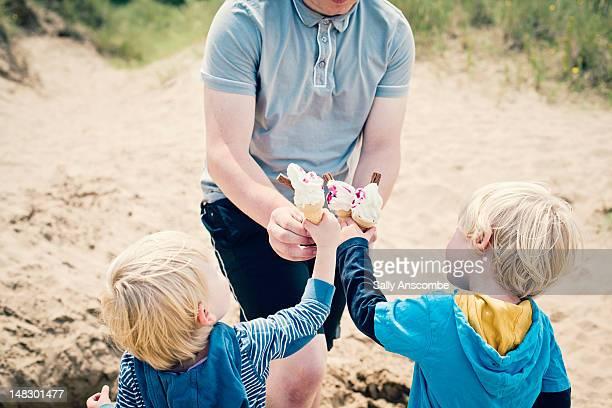 Children having ice cream cones on the beach