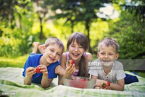 Children having picnic and eating strawberries in garden