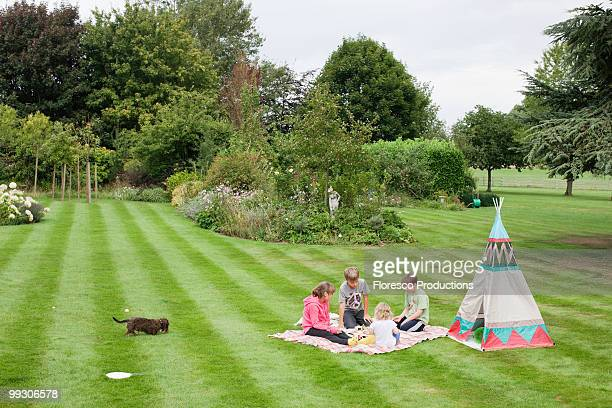 Children having picnic beside teepee