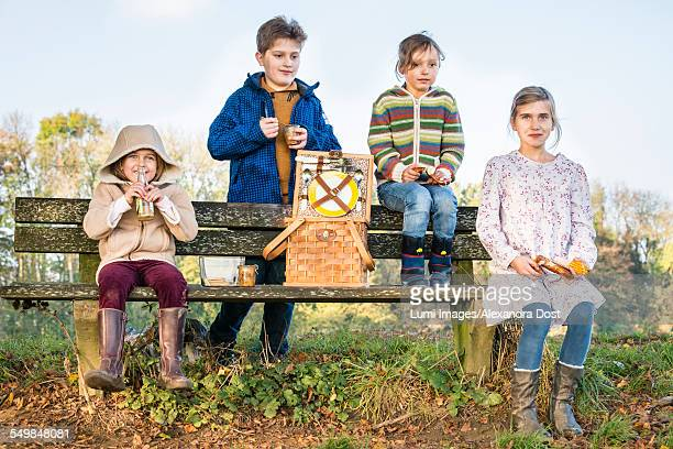 children having picnic outdoors - alexandra dost stock-fotos und bilder