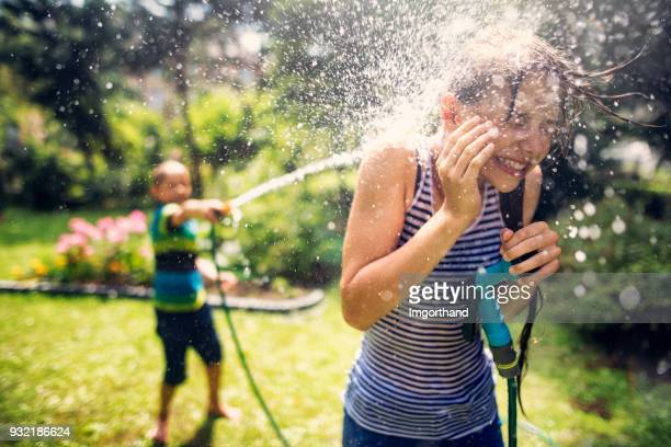 Children having splashing fun in back yard