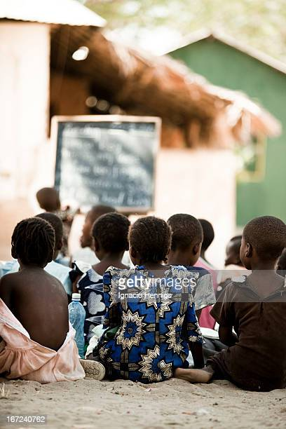 Children having tuition under a palm tree during the holidays in Tsunza Village, Coast Province, Kenya