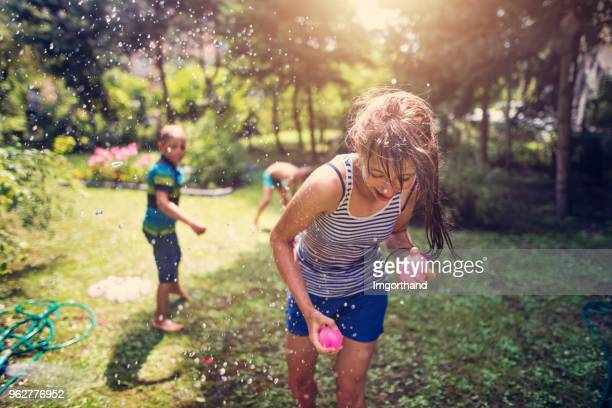 children having water balloon fight - girl fight stock photos and pictures