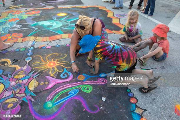 children help artist with her street art work at lake worth street painting festival - artistic product stock pictures, royalty-free photos & images