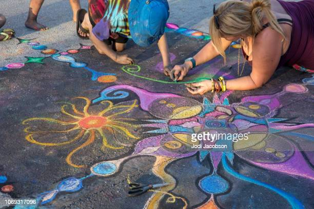children help artist with her street art work at lake worth street painting festival - chalk art equipment stock pictures, royalty-free photos & images