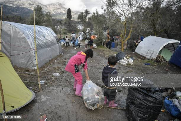 Children help clean the makeshift migrant camp after a rainfall hit the island of Chios on December 11 2019 where thousands of refugees and migrants...