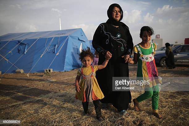 Children help their blind mother through a temporary displacement camp set up next to a Kurdish checkpoint on June 13, 2014 in Kalak, Iraq. Thousands...