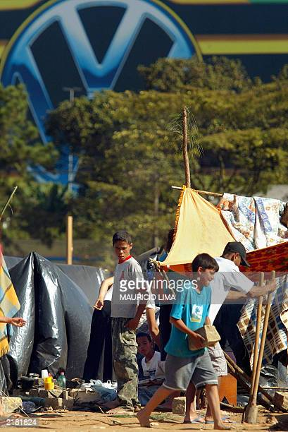 Children help their families to erect tents in a parcel of land belonging to an inactive Volkswagen factory 21 July 2003 in Sao Bernardo do Campo, 25...