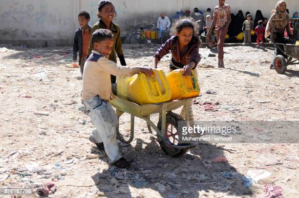 Children help their older sister to move a wheelbarrow carrying jerry cans after they collected clean water from a charity water pipe on November 18...