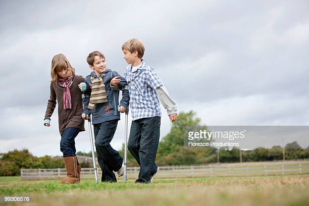 children helping boy on crutches - crutches stock photos and pictures