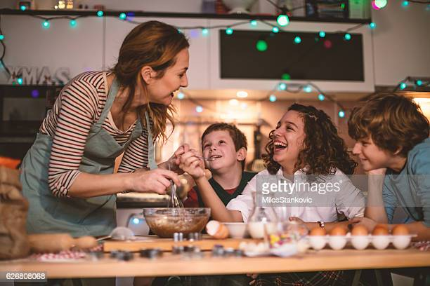 Children helping mother baking cookies for Christmas Eve