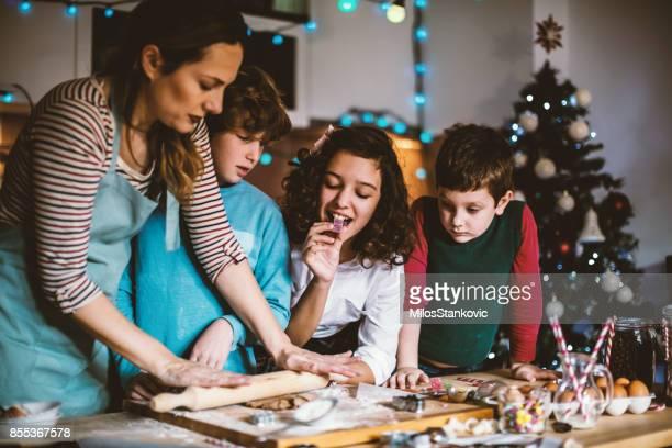 Kinderen helpen moeder bakken koekjes voor kerstavond