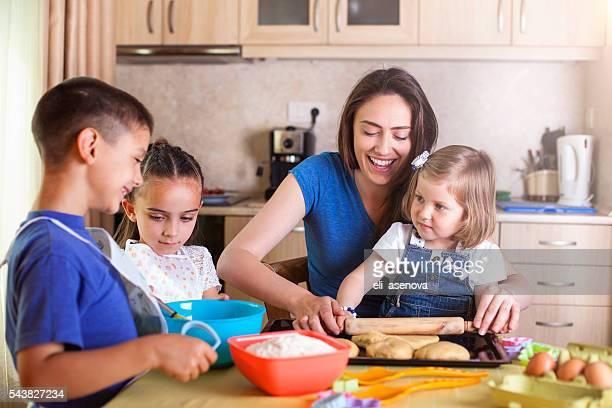 Children helping mother baking cookies