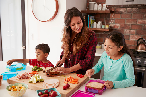 Children Helping Mother To Make School Lunches In Kitchen At Home 1006539062